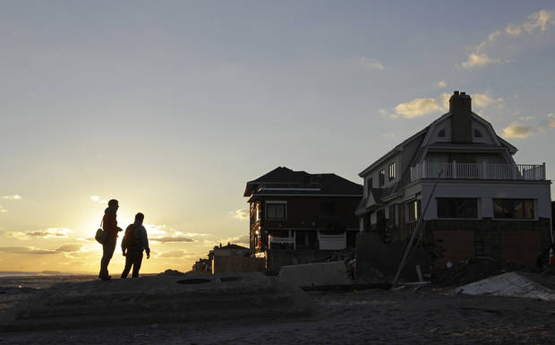 A couple pauses against the backdrop of the sunset as they walk the beach in the heavily storm-damaged section of Belle Harbor in the Queens borough of New York, Wednesday, Dec. 5, 2012.  (AP Photo/Kathy Willens)
