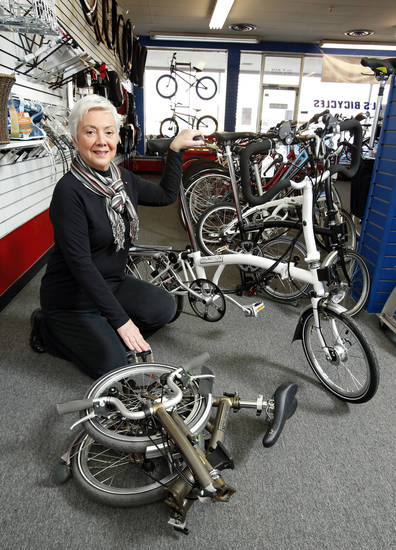 Ann Ryan, co-owner of Al's Bicycles, shows a folded and an unfolded Brompton bicycle as she explains how folding bicycles work and why they are gaining popularity. <strong>STEVE SISNEY - THE OKLAHOMAN</strong>
