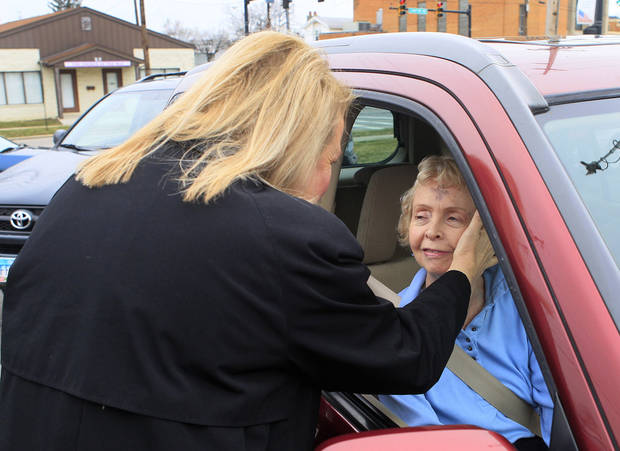 The Rev. Patricia Anderson Cook gives the blessing to Shirley Payne as she sits inside her car during drive thru Ash Wednesday services at Mt. Healthy United Methodist Church, Wednesday, Feb. 22, 2012, in Mt. Healthy, Ohio. (AP Photo/Al Behrman)