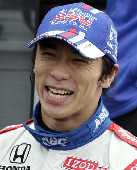 Takuma Sato, of Japan, smiles as he talks to a crew member after having the fastest time during practice for IndyCar series Honda Grand Prix of St. Petersburg auto race Saturday, March 23, 2013, in St. Petersburg, Fla. (AP Photo/Chris O'Meara)