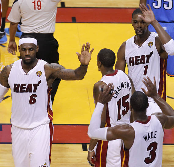 Miami Heat players LeBron James (6), Mario Chalmers (15), Chris Bosh (1) and Dwyane Wade (3) react after a play against the Oklahoma City Thunder during the first half at Game 3 of the NBA Finals basketball series, Sunday, June 17, 2012, in Miami. (AP Photo/Wilfredo Lee) ORG XMIT: NBA125