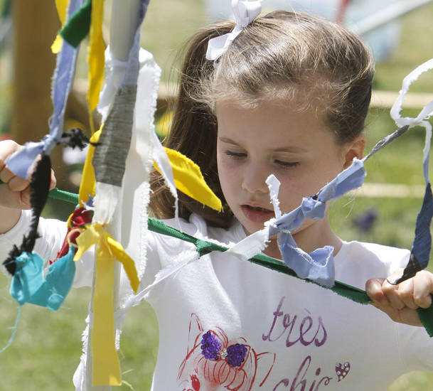"Six year old Lauren Hugo ties a ribbon onto a mass of other ribbons as a part of the ""Creation Station"" at the Festival of the Arts in downtown Oklahoma City, OK, Thursday, April 25, 2013,  By Paul Hellstern, The Oklahoman"