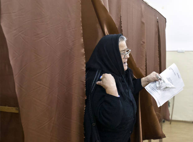 An elderly woman exits a voting cabin in Sintesti, Romania, Sunday, Dec. 9, 2012. Millions of Romanians braved rain and snow Sunday as they went to the polls for a parliamentary election that center-left government is expected to win a, but the result could lead to more of the political instability that has plagued the impoverished Balkan nation this year. (AP Photo/Vadim Ghirda)