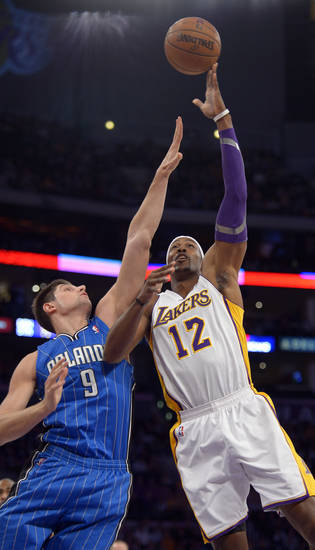 Los Angeles Lakers center Dwight Howard, right, puts up a shot as Orlando Magic center Nikola Vucevic, of Montenegro, defends during the first half of their NBA basketball game, Sunday, Dec. 2, 2012, in Los Angeles. (AP Photo/Mark J. Terrill)