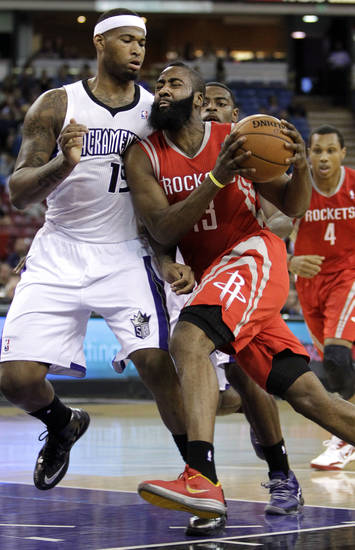 Houston Rockets guard James Harden, right, tries to drive against Sacramento Kings center DeMarcus Cousins, left, during the first quarter of an NBA basketball game in Sacramento, Calif., Wednesday, April 3, 2013. (AP Photo/Rich Pedroncelli)