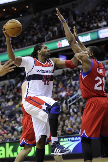 Washington Wizards center Nene (42), of Brazil, drives to the basket against Philadelphia 76ers forward Thaddeus Young (21) during the second half of an NBA basketball game on Sunday, March 3, 2013, in Washington. The Wizards won 90-87. (AP Photo/Nick Wass)
