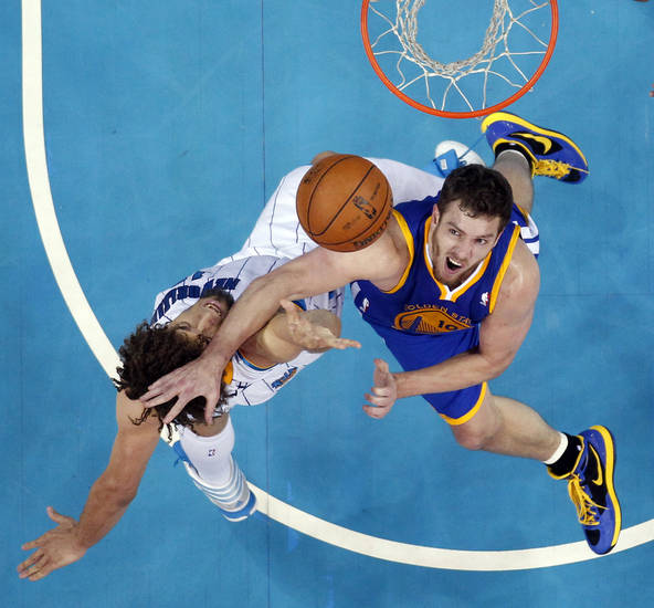 Golden State Warriors forward David Lee (10) tries to block a shot by New Orleans Hornets center Robin Lopez in the first half of an NBA basketball game in New Orleans, Monday, March 18, 2013. (AP Photo/Gerald Herbert)