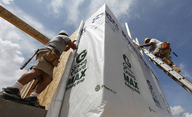 FILE - In this May 16, 2012 file photo, construction workers wrap a home in protective sheeting as they frame a new home in Chester, Va. After a six-year slump that sent more than 4 million homes into foreclosure and shrank home prices about one-third nationwide, the U.S. housing market began to recover in 2012. Modest job gains and record-low mortgage rates fueled demand. (AP Photo/Steve Helbe, File)
