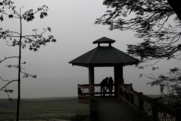 An Indian couple stand near the river Brahmaputra in Gauhati, India, Tuesday, Jan. 8, 2013. North India continues to face below average weather conditions with dense fog affecting flights and trains. (AP Photo/Anupam Nath)