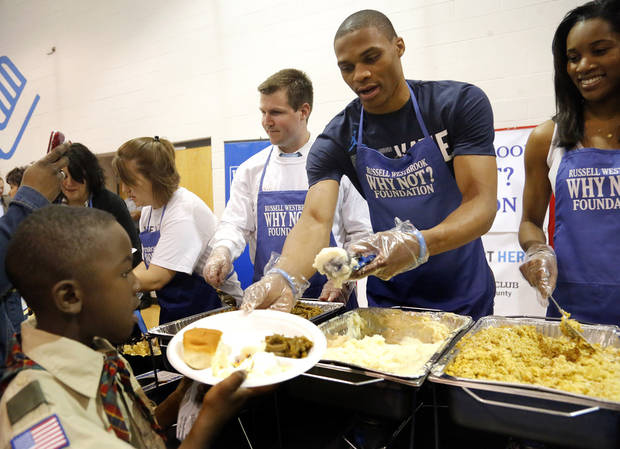 The Thunder�s Russell Westbrook serves Kendrell Fox during a Thanksgiving dinner at the Boys & Girls Club of Oklahoma County on Tuesday.  Photo by Sarah Phipps, The Oklahoman