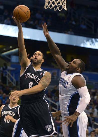 Brooklyn Nets guard Deron Williams (8) puts up a shot in front of Orlando Magic forward Glen Davis (11) during the first half of an NBA basketball game in Orlando, Fla., Friday, Nov. 9, 2012. (AP Photo/Phelan M. Ebenhack)