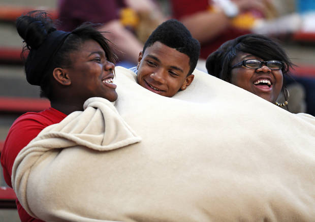From left, Putnam City North freshman Abreanna Wrice, Diego Gray and Kiana Evans try to keep warm under a blanket as they share a laugh while watching a high school football game between Mustang and Putnam City North in Mustang, Okla., Friday, Sept. 7, 2012. Photo by Nate Billings, The Oklahoman