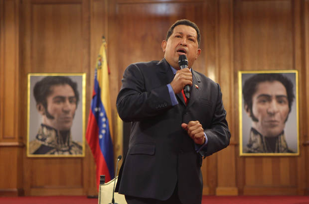 Backdropped by portraits of independence hero Simon Bolivar, Venezuela's President Hugo Chavez talks during a press conference at the Miraflores palace in Caracas, Venezuela, Tuesday, Oct. 9, 2012. The 58-year-old former military officer Chavez won his fourth consecutive presidential bid Sunday and shows no signs of ballot fatigue. (AP Photo/Rodrigo Abd)