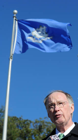 Alabama Gov. Robert Bentley soeaks during a Remembrance for the victims of the Sandy Hook Elementary School shooting during a ceremony Friday, Dec. 21, 2012, near the Connecticut state flag at the Capitol in Montgomery, Ala. (AP Photo/AL.com, Julie Bennett)