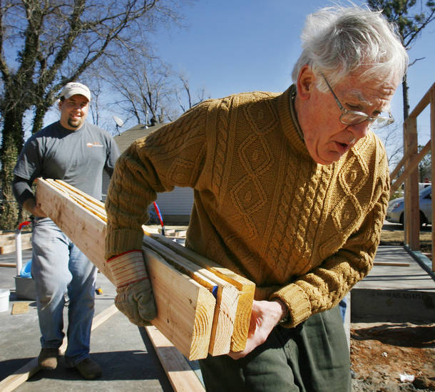 Josh Carson, construction manager, and Wake Bowser carry lumber as volunteers and Habitat for Humanity staff raise walls for a home at 313 W Himes in Norman, Okla. on Friday, Feb. 6, 2009.   Photo by Steve Sisney, The Oklahoman