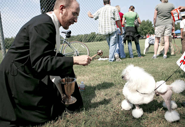 Left: The Rev. John Lock of All Souls Episcopal Church blesses Butler. PHOTOS BY JOHN CLANTON, THE OKLAHOMAN