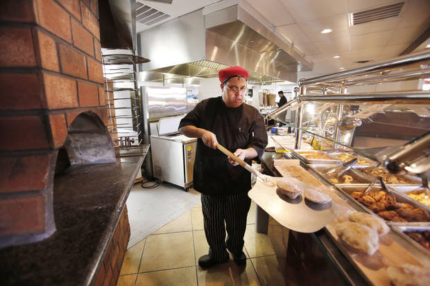 Chef Nordeen Bennai pulls pita fresh from the oven at Capers Mediterranean Buffet and Bistro. <strong>STEVE GOOCH - THE OKLAHOMAN</strong>
