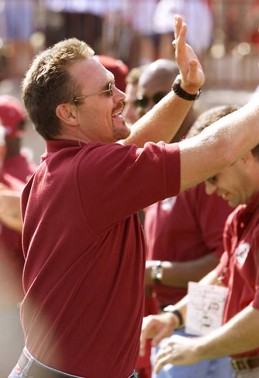In this photo from 2000, former Sooner standout Brian Bosworth slaps hands with his former teammates as he is introduced to the crowd in Memorial Stadium. The 1985 championship team was being honored at the game. PHOTO BY DOUG HOKE, The Oklahoman Archives