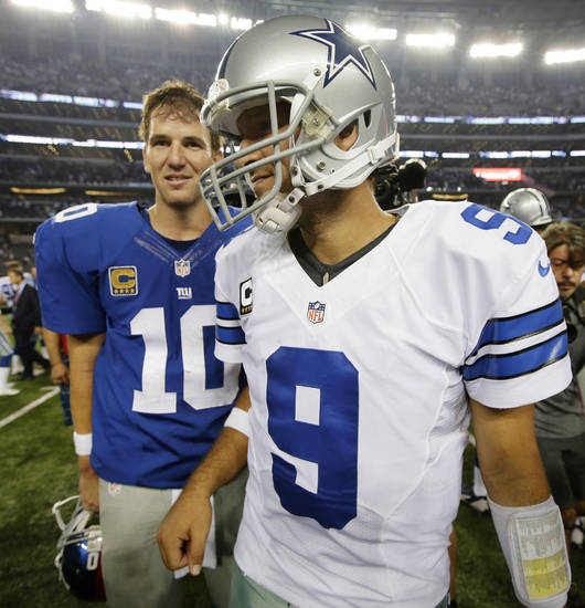 New York Giants quarterback Eli Manning (10) and Dallas Cowboys quarterback Tony Romo (9) leave the field after the Cowboys won an NFL football game 36-31 on Sunday, Sept. 8, 2013, in Arlington, Texas. (AP Photo/Tony Gutierrez)