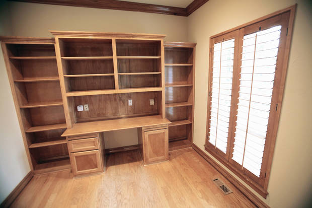 The study of the foreclosed house at 8012 NE 140 features wall-to-wall bookshelves over and around the desk area.