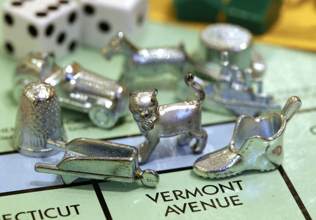The newest Monopoly token, a cat, center, rests on a Boardwalk deed next to other tokens still in use including the wheelbarrow, left, and the shoe, right, Tuesday at Hasbro Inc. headquarters, in Pawtucket, R.I. Voting on Facebook determined that the cat would replace the iron token. AP Photos