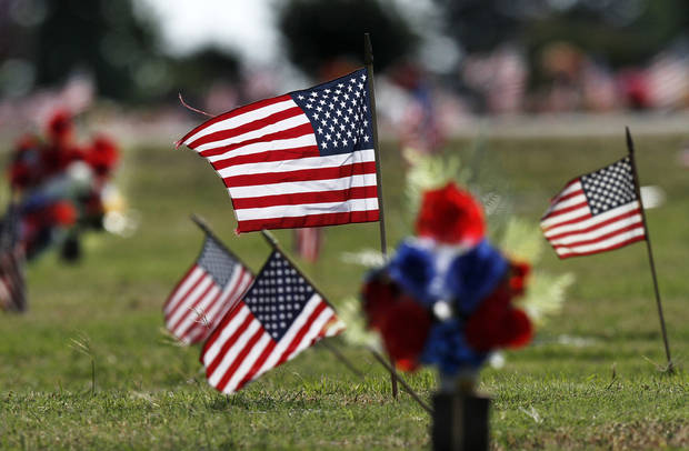 This grave seen Monday in Arlington Memory Gardens at NE 36 and Midwest Boulevard was decorated with flowers and flags. Photo by Jim Beckel, The Oklahoman