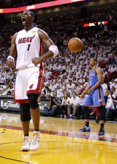 Miami's Chris Bosh (1) celebrates in front of Oklahoma City's Russell Westbrook (0) during Game 4 of the NBA Finals between the Oklahoma City Thunder and the Miami Heat at American Airlines Arena, Tuesday, June 19, 2012. Oklahoma City lost 104-98. Photo by Bryan Terry, The Oklahoman