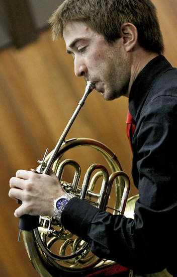 Kenji Scott Hood plays the French horn.