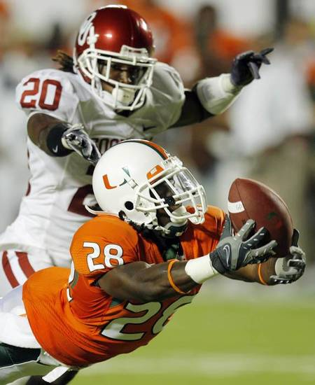 Miami's Thearon Collier (28) just misses catching a pass in front of OU's Quinton Carter (20) during the college football game between the University of Oklahoma (OU) Sooners and the University of Miami (UM) Hurricanes at Land Shark Stadium in Miami Gardens, Florida, Saturday, October 3, 2009. Miami won, 21-20. Photo by Nate Billings, The Oklahoman ORG XMIT: KOD