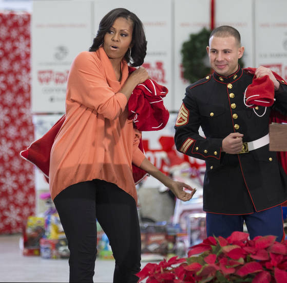First lady Michelle Obama, left, escorted by a Marine Sergeant, carries a bag of presents during her visit at the Joint Base Anacostia-Bolling to deliver toys and gifts to the Marine Corps' Toys for Tots campaign in Washington, Tuesday, Dec. 11, 2012.  (AP Photo/Manuel Balce Ceneta)