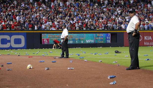 Atlanta Braves officials pick up trash on the field as security stand by during the eighth inning of the National League wild card playoff baseball game against the St. Louis Cardinals, Friday, Oct. 5, 2012, in Atlanta. The Cardinals won baseball's first wild-card playoff, taking advantage of a disputed infield fly call that led to a protest and fans littering the field with debris to defeat the Braves 6-3. (AP Photo/Todd Kirkland)