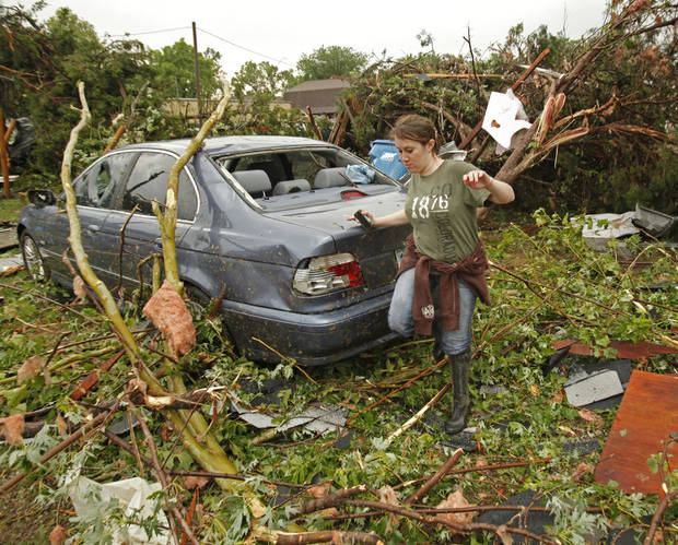 April Stout navigates her front yard beside her car after a tornado-spawning storm swept through the state on Tuesday, May 24, 2011, in Newcastle, Okla. Photo by Steve Sisney, The Oklahoman ORG XMIT: KOD