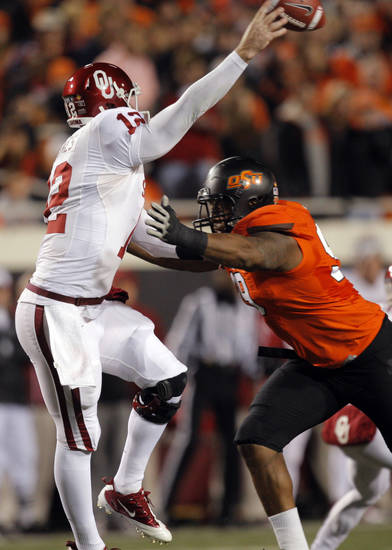 Oklahoma State&#039;s Richetti Jones (99) pressures Oklahoma&#039;s Landry Jones (12) as he throws the ball during the Bedlam college football game between the Oklahoma State University Cowboys (OSU) and the University of Oklahoma Sooners (OU) at Boone Pickens Stadium in Stillwater, Okla., Saturday, Dec. 3, 2011. Photo by Sarah Phipps, The Oklahoman