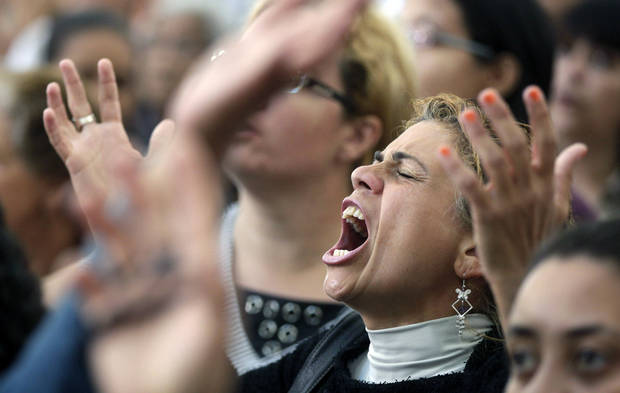 A woman sings during a Mass led by Catholic priest Marcelo Rossi at the Mother of God sanctuary in Sao Paulo, Brazil, Saturday, Nov. 3, 2012. Rossi, a Latin Grammy-nominated Christian music singer and author of best-selling books in Brazil, inaugurated on Friday the massive new Roman Catholic church that will hold about 20,000 worshippers when complete. (AP Photo/Andre Penner)