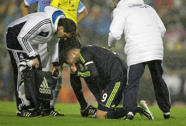 Real Madrid's Karim Benzema from France is attended to by club medics after getting hurt during the 1st leg of a last-16 Copa del Rey soccer match against Celta at the Balaídos stadium in Vigo, Spain, Wednesday Dec. 12, 2012. (AP Photo/Lalo R. Villar)