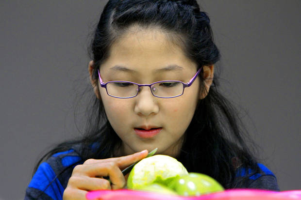 Christie Yang, 11. peels an apple as she and other teens participate in an apple pie-baking workshop.