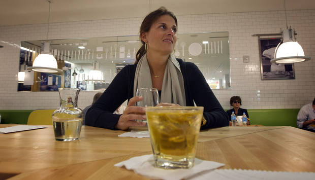 In this Wednesday, Nov. 14, 2012 photo, Liz Lamoureux sits in the Food Network Kitchen at the Fort Lauderdale-Hollywood International Airport, in Fort Lauderdale, Fla., sipping a glass of wine before her flight back to San Antonio. Dining-on-the-go is soaring at the airport where travelers can dine at a restaurant inspired by a test kitchen. (AP Photo/J Pat Carter)