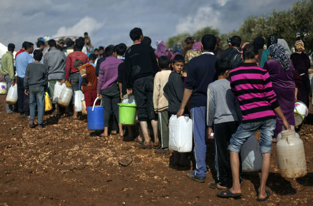 Syrians who fled from the violence in their village, carry plastic containers as they line up to fill them with water at a displaced camp, in the Syrian village of Atma, near the Turkish border with Syria. Saturday, Nov. 10, 2012. (AP Photo/ Khalil Hamra)