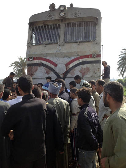 Egyptians gather at the scene of a train crash that killed at least 47 people, most of them children near Assiut in southern Egypt, Saturday, Nov. 17, 2012. The bus was carrying more than 50 children between 4 and 6 years old when it was hit near al-Mandara village in Manfaloot district in the province of Assiut, a security official said, adding that it appears that the railroad crossing was not closed as the train sped toward it. (AP Photo/Mamdouh Thabet)