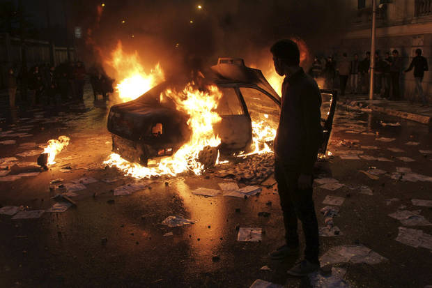 A masked protester watches a vehicle burn during clashes between opponents of Egyptian President Mohammed Morsi and his Islamist supporters in Alexandria, Egypt, Friday, Dec. 21, 2012. Thousands of Islamists clashed with their opponents on Friday in Egypt's second largest city, Alexandria as the two sides hurled stones and youth protesters sat fire on vehicles belonging to Islamists, a day before the second leg of voting on a proposed constitution that has deeply polarized the nation.(AP Photo)