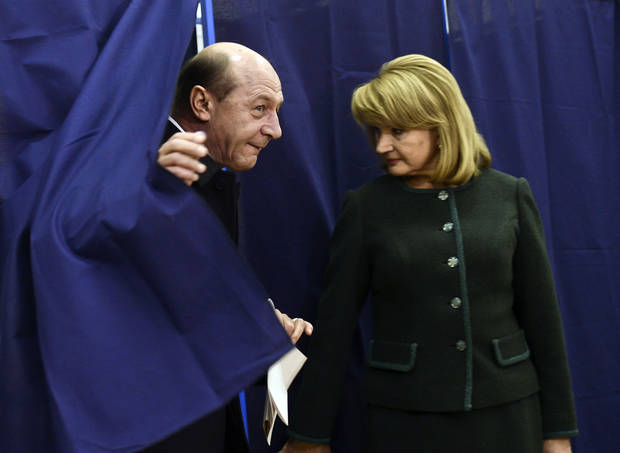 Romania&#039;s President Traian Basescu, left, exits a voting cabin as his wife Maria, right, stands by, in Bucharest, Romania, Sunday, Dec. 9, 2012. Millions of Romanians braved rain and snow Sunday as they went to the polls for a parliamentary election that center-left government is expected to win a, but the result could lead to more of the political instability that has plagued the impoverished Balkan nation this year. (AP Photo)