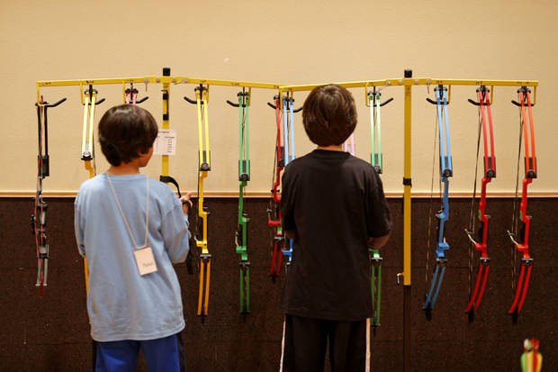 Students pick out their bows before an archery class at the Edmond Multipurpose Activity Center.  PHOTOS BY BRYAN TERRY, THE OKLAHOMAN