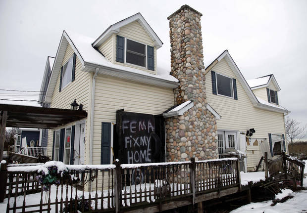 A sign is displayed on a house damaged by Superstorm Sandy in the Oakwood Beach section of Staten Island, New York, Thursday, Nov. 8, 2012. (AP Photo/Seth Wenig) ORG XMIT: NYSW108
