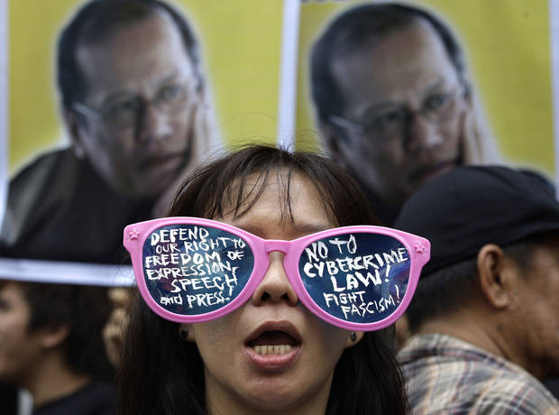   A protester, wearing sunglasses with slogans, stands in front of picture of Philippine President Benigno Aquino III during a rally against the anti-cybercrime law in front of the Supreme Court in Manila, Philippines on Tuesday, Oct. 9, 2012. The Philippine Supreme Court on Tuesday suspended implementation of the country&#039;s anti-cybercrime law while it decides whether certain provisions violate civil liberties. (AP Photo/Aaron Favila)  