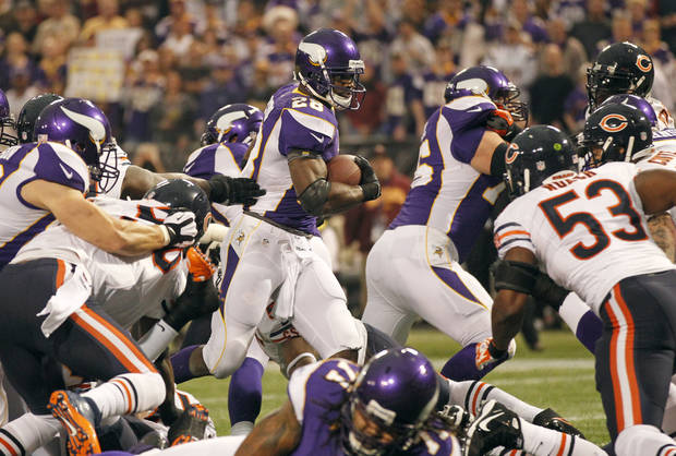 Minnesota Vikings running back Adrian Peterson, center, scores on a 1-yard touchdown run during the first half of an NFL football game against the Chicago Bears Sunday, Dec. 9, 2012, in Minneapolis. (AP Photo/Andy King)