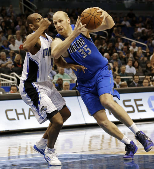 Dallas Mavericks' Chris Kaman (35) drives to the basket past Orlando Magic's Arron Afflalo, left, during the first half of an NBA basketball game, Sunday, Jan. 20, 2013, in Orlando, Fla. (AP Photo/John Raoux)