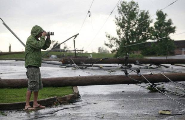 A photographer shoots some of the damage near St. Joseph Hospital in Joplin, Mo., after the town was hit by a tornado on Sunday, May 22, 2011. (AP Photo/The Wichita Eagle, Jaime Green) ORG XMIT: KSWIE105