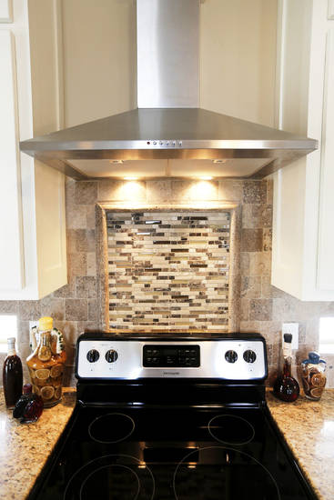 A detailed tile backsplash adds texture and style to the kitchen of the TimberCraft model home at 8440 NW 142.