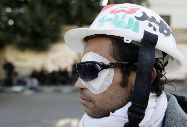 "A protester injured in his eye from recent clashes looks on in front of the presidential palace in Cairo, Egypt, Thursday, Dec. 13, 2012. Egypt's opposition called on its followers to vote ""no"" in a crucial referendum on a disputed constitution drafted by Islamist supporters of President Mohammed Morsi. (AP Photo/Hassan Ammar)"