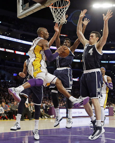 Los Angeles Lakers guard Kobe Bryant (24) passes as Oklahoma City Thunder center Hasheem Thabeet, center, and forward Nick Collison (4) defend in the first half of an NBA basketball game in Los Angeles, Sunday, Jan. 27, 2013. The Lakers won 105-96. (AP Photo/Reed Saxon) ORG XMIT: LAS104